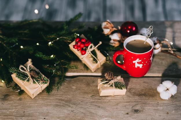 Tasse kaffee mit weihnachtsschmuck auf holztisch.