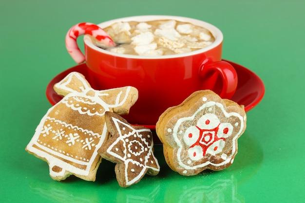 Tasse kaffee mit weihnachtssüße auf grünem hintergrund