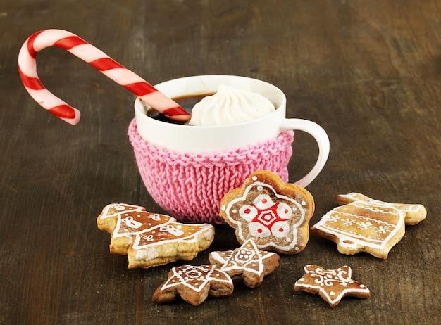 Tasse kaffee mit weihnachtssüße auf holztisch nahaufnahme