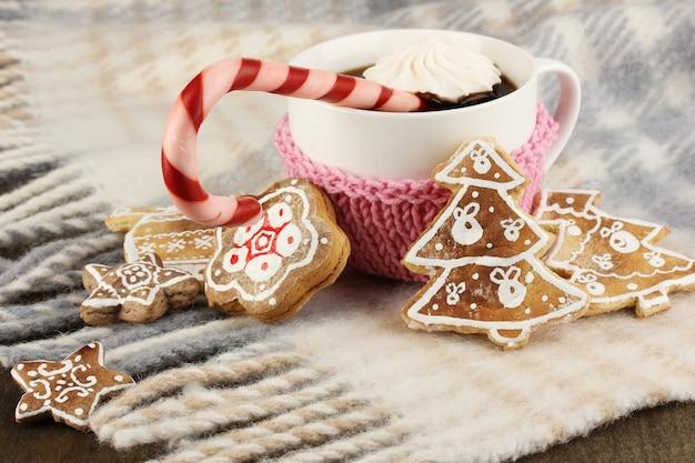 Tasse kaffee mit weihnachtssüße auf karierter nahaufnahme
