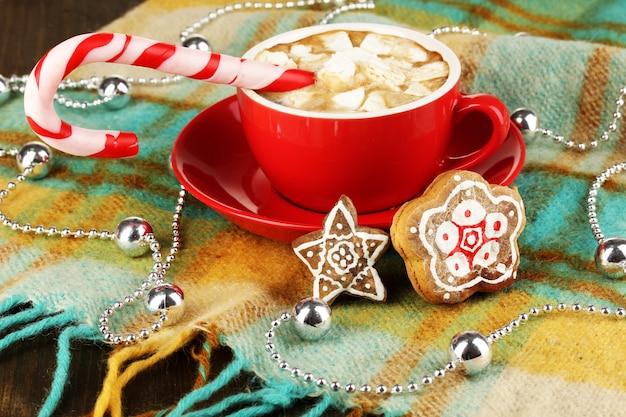 Tasse kaffee mit weihnachtssüßigkeiten auf karierter nahaufnahme close