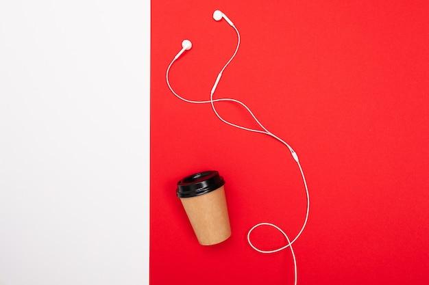 Tasse kaffee mit weißen kopfhörern auf roter und weißer wand
