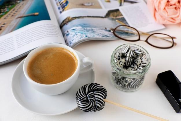 Tasse kaffee mit wirbelnden schwarzen und weißen lutscherbonbons in einem geöffneten magazin aus glas