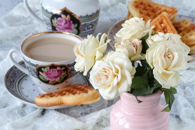 Tasse kaffee mit zarten weißen blumenrosen.