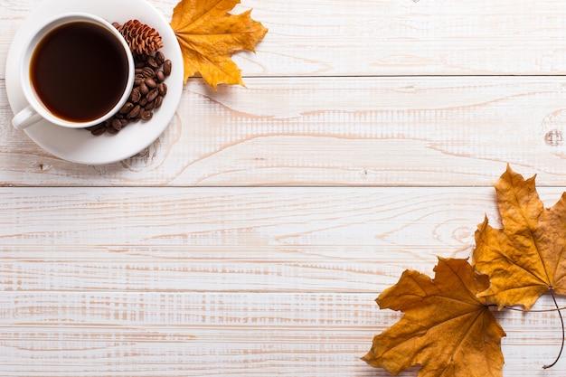 Tasse kaffee mit zerstreuten kaffeebohnen, trockene gelbe blätter auf einem holztisch. herbstmorgenstimmung, copyspace.