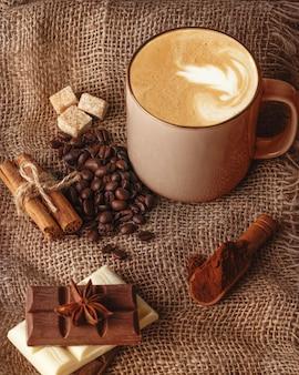 Tasse kaffee mit zimt, anis, kaffeebohne, pralinen und zucker auf einem hölzernen hintergrund