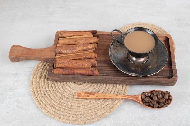Tasse kaffee mit zimtstangen auf dunklem brett und kaffeebohnen