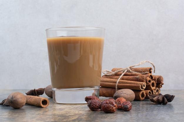 Tasse kaffee mit zimtstangen auf marmorhintergrund. hochwertiges foto
