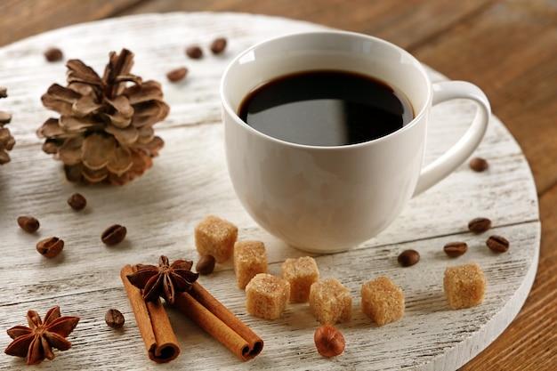 Tasse kaffee mit zucker und zimt auf weißer holzmatte