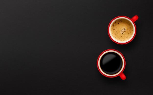 Tasse kaffee mit zwei rottönen auf schwarzem papierhintergrund. ansicht von oben