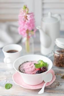 Tasse kaffee, müsli mit erdbeeren, nüssen und milch.