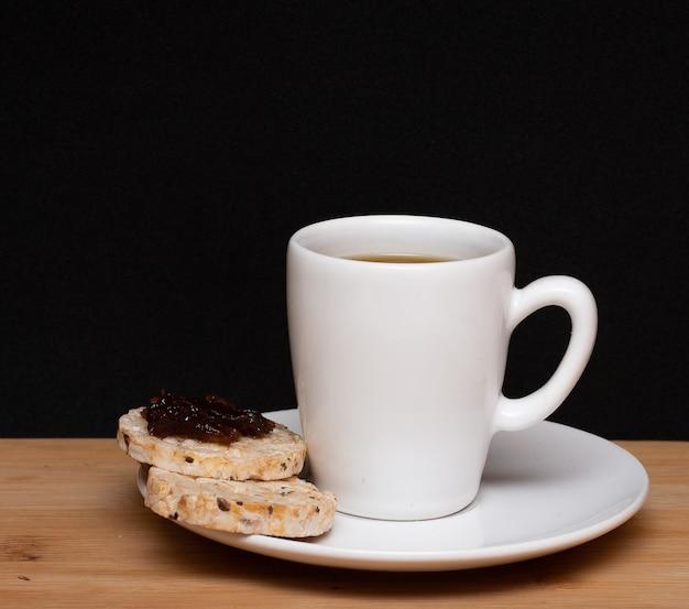 Tasse kaffee neben einem reis vegane kekse mit einem gelee auf der oberseite unter dem holztisch