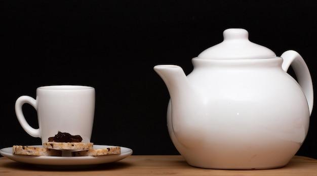 Tasse kaffee neben einem veganen reiskekse mit einem gelee oben und einer kaffeekanne unter dem holztisch