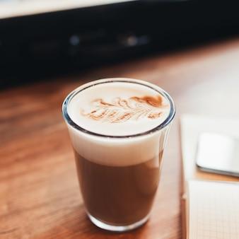 Tasse kaffee, notizbuch am tisch im café. unscharfer hintergrund.