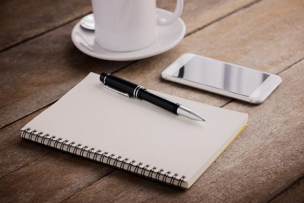 Tasse kaffee, notizbuch, stift und intelligentes telefon