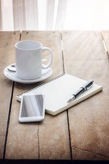 Tasse kaffee, notizbuch, stift und smartphone