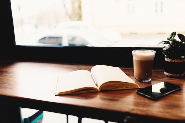 Tasse kaffee, notizbuch, telefon am tisch im café. unscharfer hintergrund. hochwertiges foto