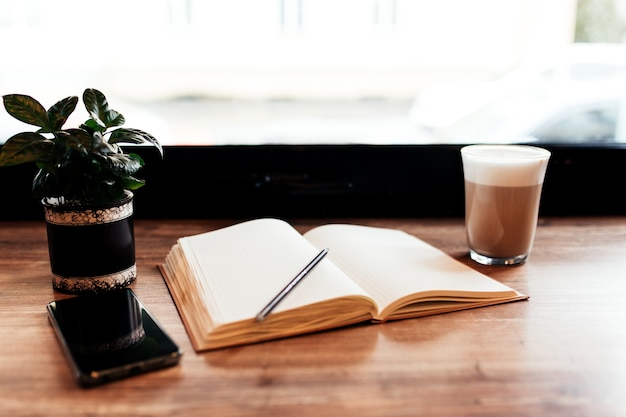 Tasse kaffee, notizbuch, telefon am tisch im café. unscharfer hintergrund.