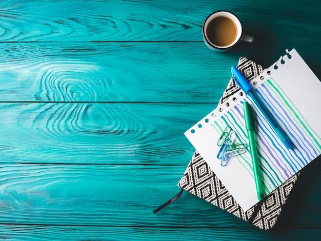Tasse kaffee, notizbuch und stift auf dunkelheit