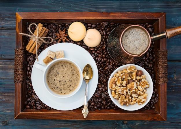 Tasse kaffee, nüsse in der schüssel, kaffeekanne, zimt, anis, zucker, kaffee auf einem holztablett