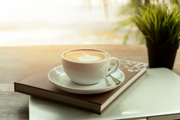 Tasse kaffee oben auf buch und laptop auf holztisch morgens.