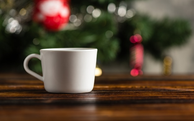 Tasse kaffee oder tee auf einem holztisch vor dem hintergrund eines weihnachtsbaumes
