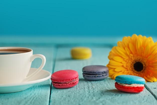 Tasse kaffee oder tee mit gelber blume und makronen auf blauem hintergrund