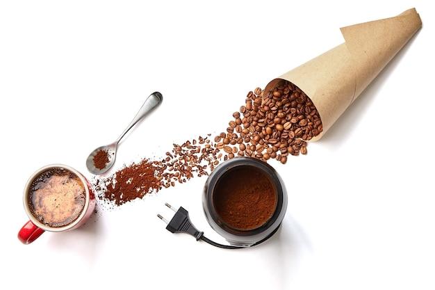 Tasse kaffee, papiertüte mit bohnen, kaffeemühle und gemahlener kaffee auf weißem hintergrund