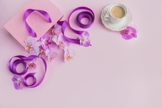 Tasse kaffee, rosa geschenktüte mit lila bändern und rosa orchideenblumen