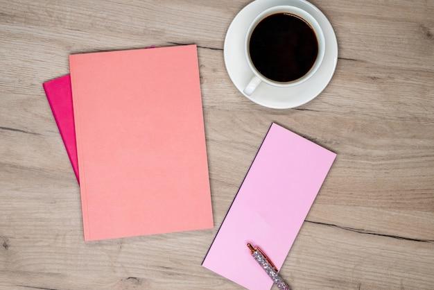 Tasse kaffee, rosa notizbuch und stift