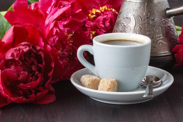Tasse kaffee, rosa pfingstrosenmuster auf holz. guten morgen