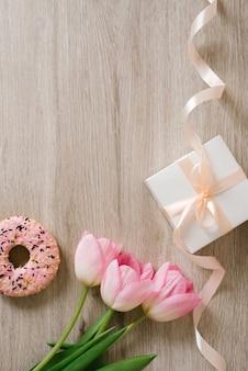 Tasse kaffee, rosa tulpen auf holzhintergrund. grüße zum frühlingsfrauentag. ansicht von oben, flach, kopienraum.