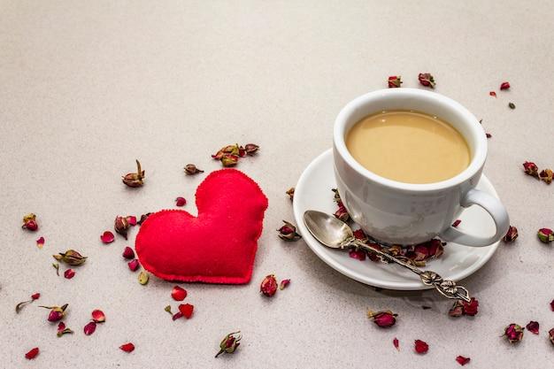 Tasse kaffee, rosenknospen und blütenblätter und rotes filzherz