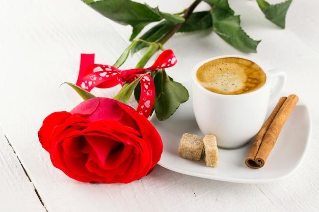 Tasse kaffee, rotrose, zucker und zimt auf einem weißen hölzernen hintergrund