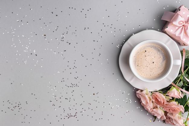 Tasse kaffee, schachtel mit einem geschenk und rosa rosen auf einer festlichen grauen oberfläche