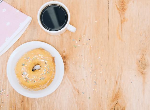 Tasse kaffee; serviette und frisch gebackener donut auf platte über holzuntergrund