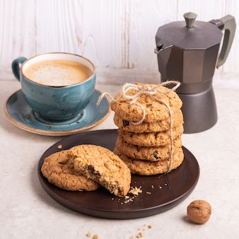 Tasse kaffee, stapel hafermehlplätzchen, kaffeemaschine, selbst gemachte bäckerei