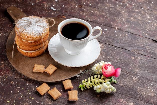 Tasse kaffee stark und heiß zusammen mit keksen und kekskuchen auf hölzernen braunen schreibtisch, obst backen kuchen kaffeekeks süß