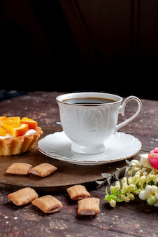 Tasse kaffee stark und heiß zusammen mit keksen und orangenkuchen auf holzschreibtisch, obst backen kaffeekeks