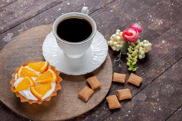 Tasse kaffee stark und heiß zusammen mit keksen und orangenkuchen auf holzschreibtisch, obst backen kuchen kaffee keks süß