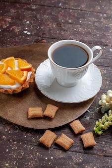 Tasse kaffee stark und heiß zusammen mit keksen und orangenkuchen auf holzschreibtisch, obstkuchen kuchen kaffeekeks