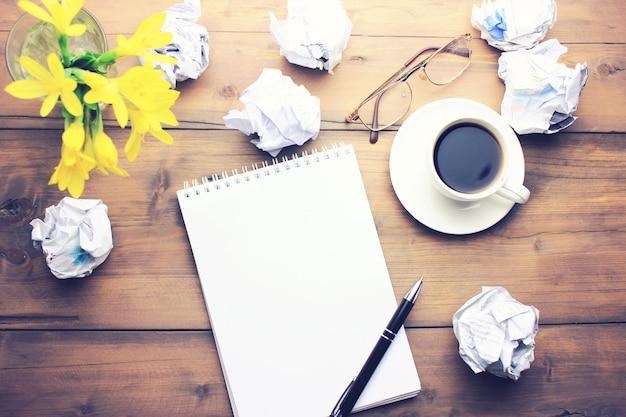 Tasse kaffee, stift, notizblock, papiere, gläser und blumen auf holztisch