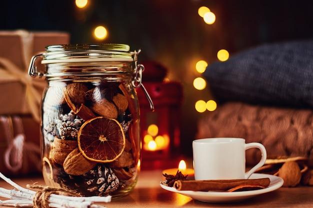 Tasse kaffee, tannenzapfen, getrocknete orangen und girlandenlichter auf einem dunklen hintergrund.