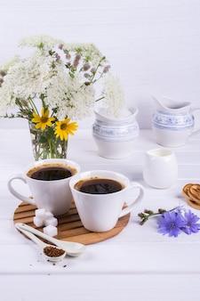 Tasse kaffee tee chicorée trinken heißes getränk mit chicorée-blume und zuckerkeksen auf einem weißen tisch. stillleben mit frühstück