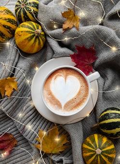 Tasse kaffee, trockene blätter und schal auf einem tisch. flache lage, draufsicht, kopierraum