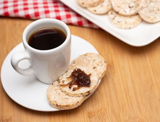 Tasse kaffee umgeben von einem reis vegane kekse unter dem holztisch