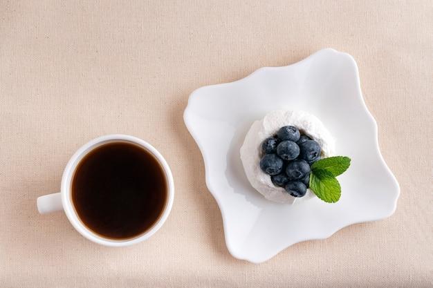 Tasse kaffee und baiser-beeren-kuchen. draufsicht. frühstück im bett.