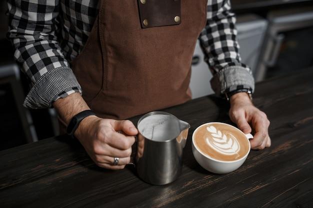 Tasse kaffee und barista hände an der bar in einem modernen café