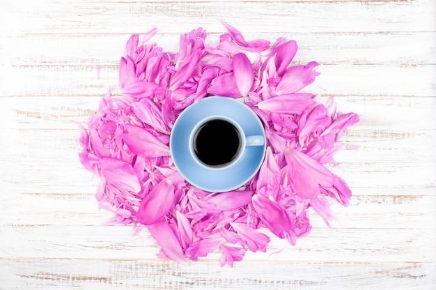 Tasse kaffee und blumenblätter von rosa pfingstrosen