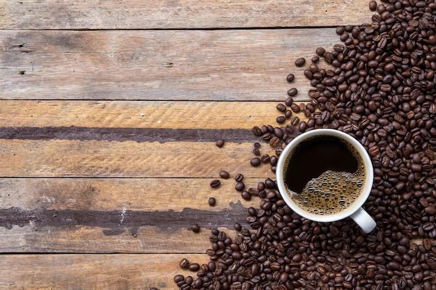 Tasse kaffee und bohne auf holzbodenhintergrund. draufsicht